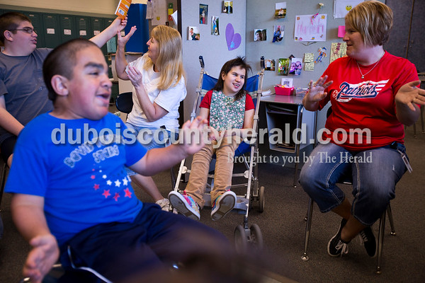 Heritage Hills eighthgrader Collin Beier, back left, seventhgrader Christian Perez, front left, and teachers Mary App and Paula Carpenter, sit around Zoe during music time at Heritage Hills Middle School on May 5.