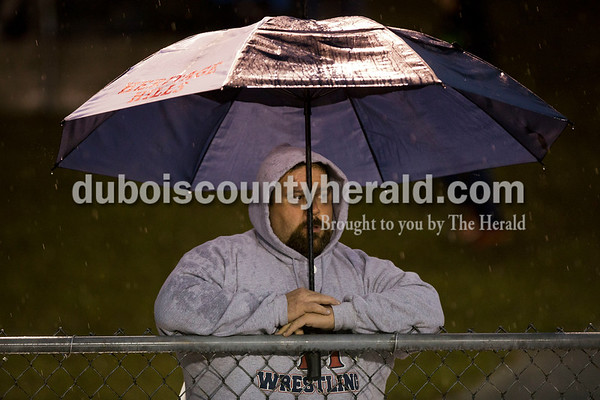Heritage Hills' fan Jerry Miller tried to stay dry under an umbrella as he watched Friday night's game in Lincoln City. Heritage Hills defeated Southridge 17-7.   Alisha Jucevic/The Herald