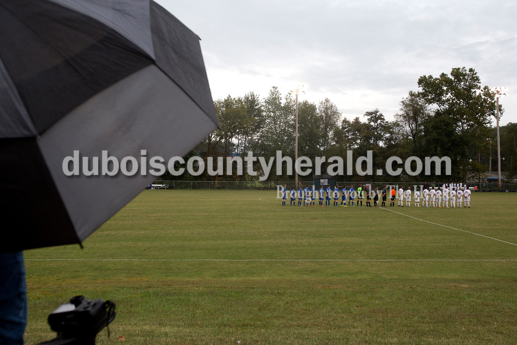 Erica Lafser/The Herald<br /> Northeast Dubois, referees and Heritage Hills lined up and faced the flag for the playing of the national anthem before Tuesday's game at Heritage Hills in Lincoln City. The Patriots won 6-0.