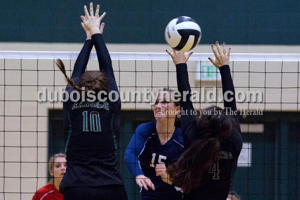 Heritage Hills' Abby Wahl spiked the ball over the net as Forest Park's Karissa Wollenmann and Katelyn Tretter jumped up in an attempt to block during Monday night's game at Forest Park High School in Ferdinand. Heritage Hills won in three sets. <br /> Alisha Jucevic/The Herald