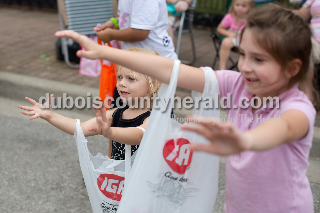 Erica Lafser/The Herald<br /> Rowynn Broshears of Troy, 3, left, and her soon to be sister Victoria Hundley of Troy, 7, reached out for the candy being thrown in their direction during the Herbstfest parade on Sunday in Huntingburg.