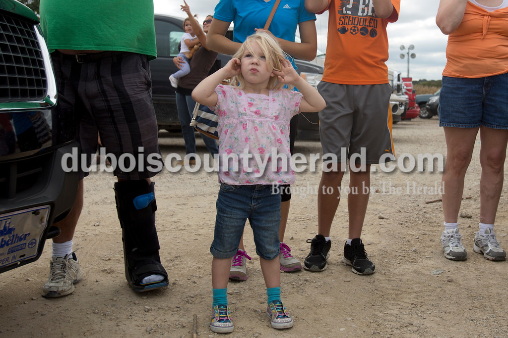 Erica Lafser/The Herald<br /> Felicity Schaefer of Evansville, 4, covered her ears as she watched the pumpkins launch through the ear during the Herbstfest on Saturday at street department lot in Huntingburg. Schaefer was attending with her godfather, Tim Jarboe of Ferdinand.