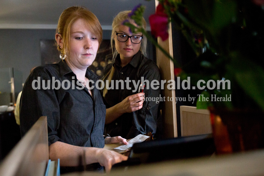 Alisha Jucevic/The Herald<br /> <br /> Jenna Stinson of Loogootee rang up a tab next to hostess Sasha Heeren of Jasper, 17, on Wednesday night at one of the Jasper's new downtown restaurants, 514. The restaurant opened in August but had to quickly end their lunch hours because of a shortage in staff. Wednesday was their first day to reopen for lunch.