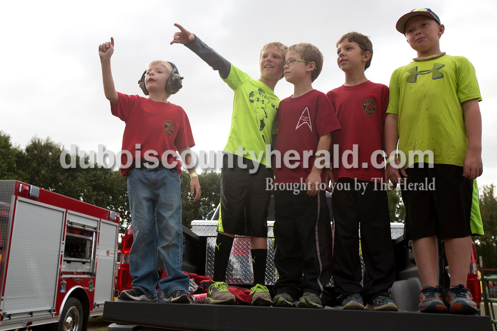 Erica Lafser/The Herald<br /> Anstin Vonderheide of St. Anthony, 6, far left, Korbyn Persohn of Huntingburg, 8, Josh Sermersheim of Huntingburg, 8, Kale Wissel of Huntingburg, 8, and Blake Beck of Huntingburg, 8, watched the demolition derby from the back of a truck on Saturday at the Dubois County 4-H Fairgrounds. All of their dad's work with the St. Henry Fire Department.