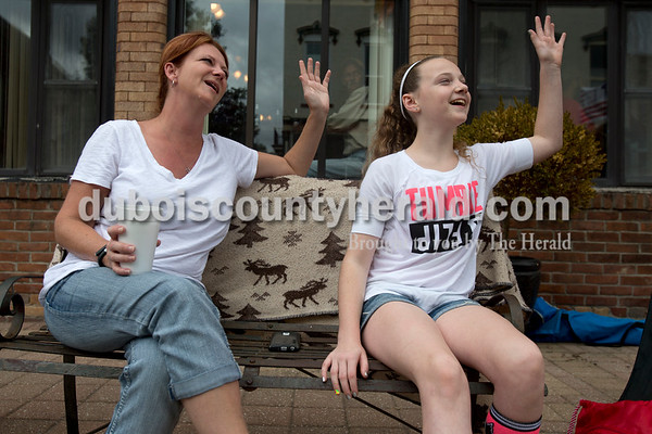 Erica Lafser/The Herald Mell Bicknell, left, of Huntingburg and her daughter Annie, 12, waved to people driving by during the Herbstfest parade on Sunday in Huntingburg.