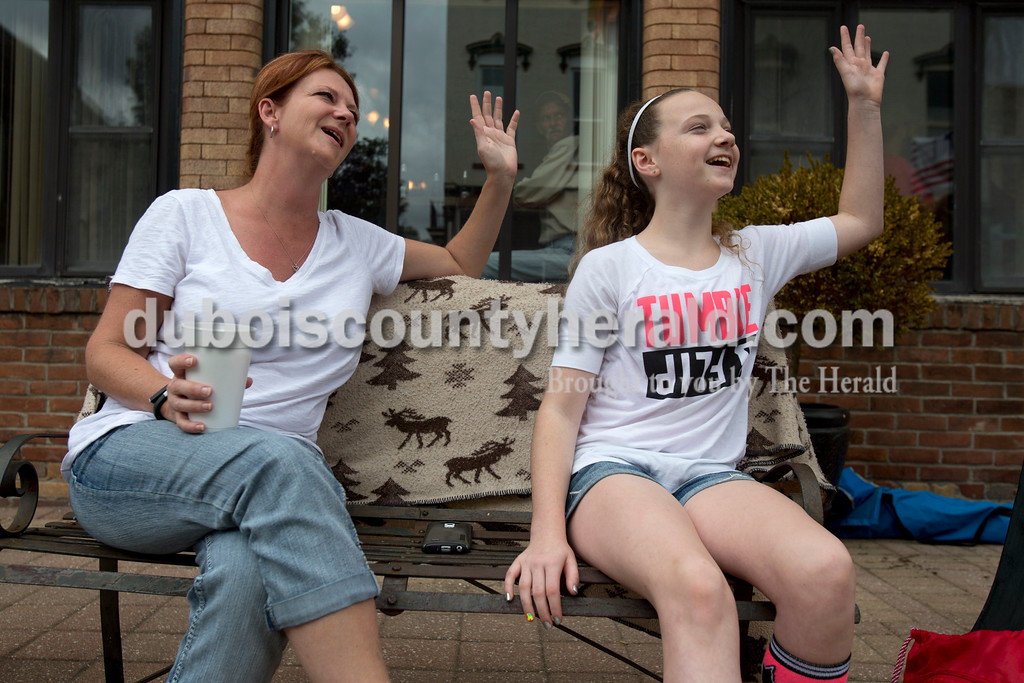 Erica Lafser/The Herald<br /> Mell Bicknell, left, of Huntingburg and her daughter Annie, 12, waved to people driving by during the Herbstfest parade on Sunday in Huntingburg.