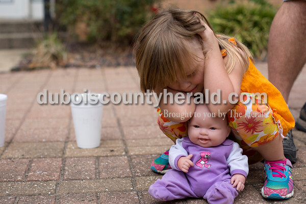 Erica Lafser/The Herald Ellie Petry of Ferdinand, 3, held her and her doll's ears during the loud sirens at the Herbstfest parade on Sunday in Huntingburg.
