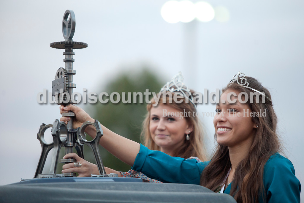 Erica Lafser/The Herald<br /> 2015 Miss Dubois County and Miss Photogenic Moriah Fleck of St. Anthony, 18, and Teen Miss Dubois County Lauren Tretter of Ferdinand, 17, presented the Mad Dog award before the lawnmower demolition derby on Saturday at the Dubois County 4-H Fairgrounds. The Mad Dog award was made by Brandon Epple of Loogootee and the parts were donated by Jasper Engines. This award was later presented to Charlie Quinn for his bold efforts in the lawnmower demolition derby.