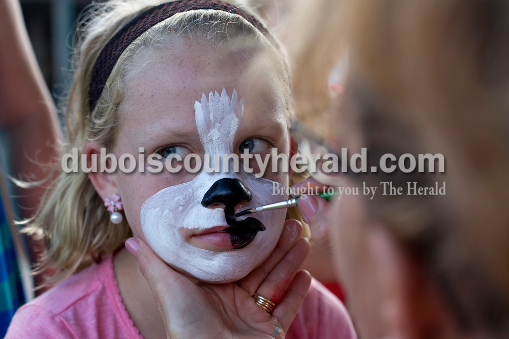 Erica Lafser/The Herald<br /> Claire Lanman of Huntingburg, 10, had a puppy with a mustache and it's tounge sticking out face painted on her by Sandi Trusty of Huntingburg during the Herbstfest on Saturday at Huntingburg City Park in Huntingburg.