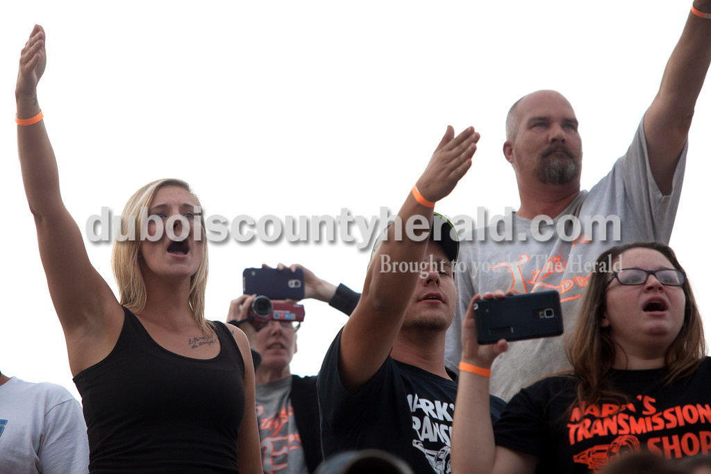 "Erica Lafser/The Herald<br /> Shana Rickenbaugh of Dubois, left, watched her husband Andy compete in the demolition derby on Saturday at the Dubois County 4-H Fairgrounds. ""I get into it, I can't help it,"" Shana said."