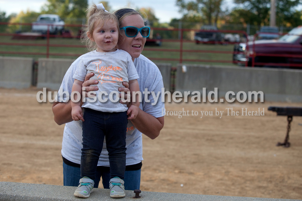 "Erica Lafser/The Herald<br /> Kesha Mullins of Jasper held her one-year-old daughter, Peyton, during her husband Chris's class of the demolition derby on Saturday at the Dubois County 4-H Fairgrounds. ""She likes cars,"" Kesha said about Peyton."