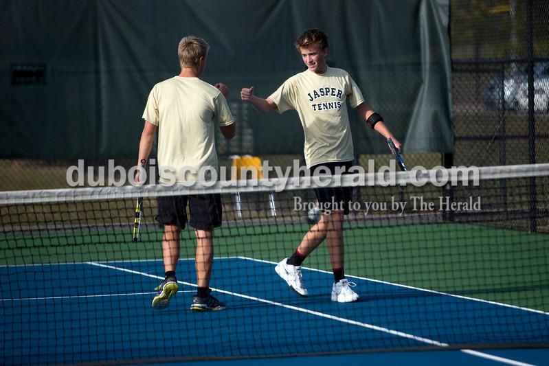 Jasper's Andrew Schmitt, left, and Hudson Schmidt celebrated a point during Wednesday's tennis sectional against Forest Park in Jasper. Ariana van den Akker/The Herald
