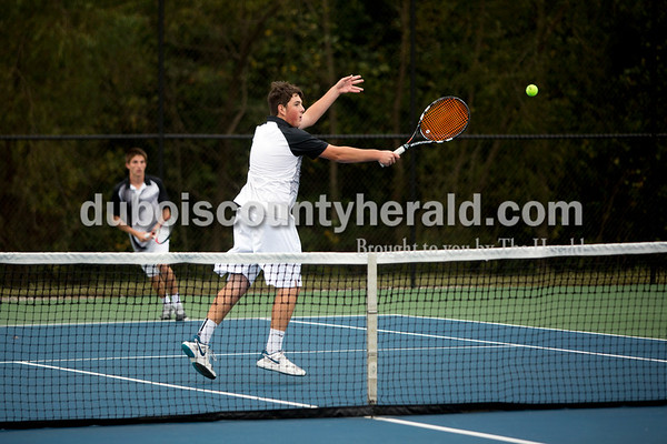 Jasper's Eli Franks popped the ball over the net during Thursday's tennis sectional championship against Pike Central in Jasper. Jasper won 5-0. Ariana van den Akker/The Herald