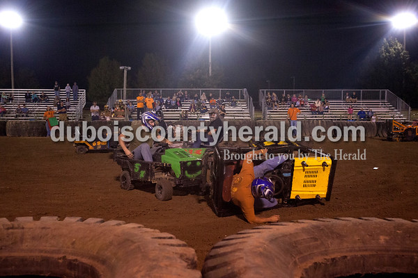 Erica Lafser/The Herald Charlie Quinn of Dale, left, knocked over Dave Lampert of Celestine during the lawnmower demolition derby on Saturday at the Dubois County 4-H Fairgrounds. Lampert made a comeback taking first place while Quinn took home second and the Mad Dog award.