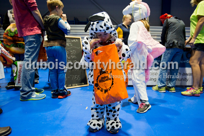 Alisha Jucevic/The Herald  <br /> Zayden Frick of Ferdinand, 2, searched through his bag of candy during the Vincennes University Jasper Campus Fright Night on Friday night at the Ruxer Gym in Jasper. VUJC students, faculty and staff decorated tableland handed out candy to the children.