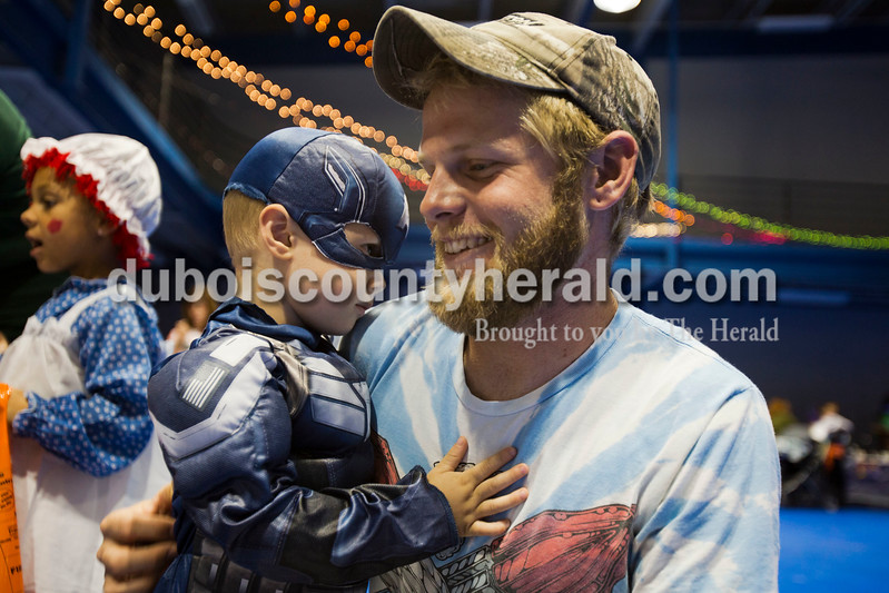 Alisha Jucevic/The Herald  <br /> Dressed in a Captain America costume, Daniel Creutz, 3, stood with his father, Josh, both of Jasper, during the Vincennes University Jasper Campus Fright Night on Friday night at the Ruxer Gym in Jasper. VUJC students, faculty and staff decorated tableland handed out candy to the children.