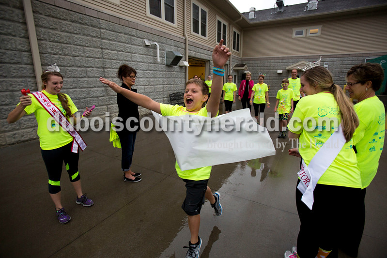 Alisha Jucevic/The Herald <br /> Dakota Roach of Crystal, 12, broke through the start line banner during the Illuminating Life 5k walk and run put on by Miss Indiana Sr. Sweetheart 2016, Priscilla Olson of Jasper, 16, left, on Saturday evening at Northwood Retirement Community in Jasper. Olson has volunteered at the nursing home for five years, and she put on this event to help senior citizens and bring awareness to their value in the Jasper community. Olson hopes to make this an annual event in Jasper.