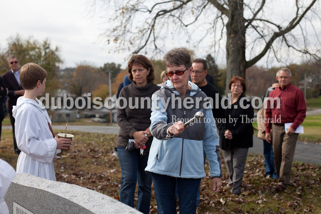 """Erica Lafser/The Herald<br /> Jeanie Huff of Huntingburg splashed Holy water on the """"Monument to the Unborn"""" on Sunday at St. Mary's Church Huntingburg in Huntingburg. This gift of remembrance from the Monsignor Leonard Wernsing Knights of Columbus will be the final monument placed in all Catholic cemeteries throughout Dubois County."""