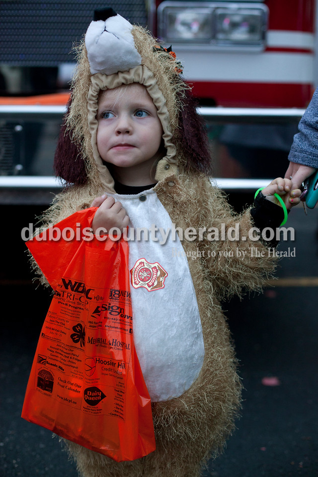 """Erica Lafser/The Herald<br /> Claire Terwiske of Jasper, 3, held the hand of her mom, Melissa, during the """"Trick-or-Treating at the Fire Station"""" event on Saturday at the Huntingburg City Hall parking lot in Huntingburg. The party geared for 12 year olds and younger let kids look inside fire trucks and police cars. """"(Claire) loves her doggy costume, she's been wearing it for weeks,"""" Melissa said."""