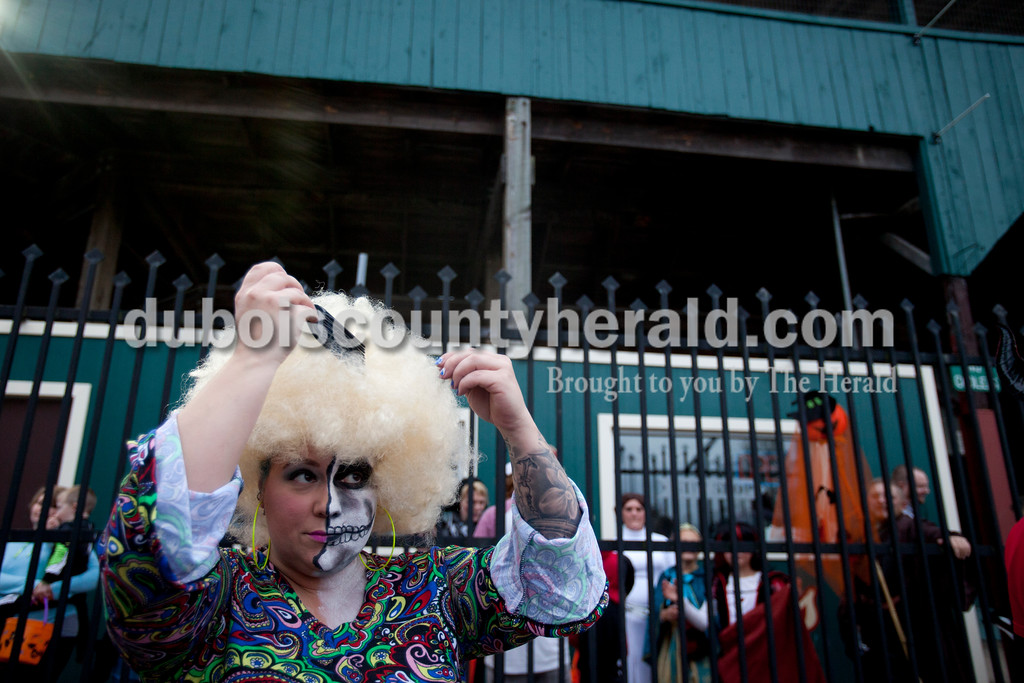 Erica Lafser/The Herald<br /> Ashley Lueken of Jasper picked her hair to add some volume while she waited in line for the trick-or-trail event on Saturday hosted by the Huntingburg United Methodist Church at League Stadium in Huntingburg. The trail had several booths for children to receive candy or trinkets.