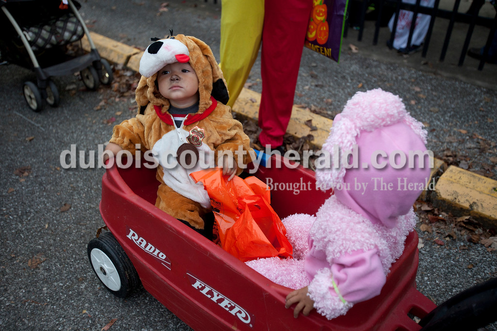 Erica Lafser/The Herald<br /> Edward Chavez of Huntingburg, 2, waited in line with his twin sister Elizabethe for the trick-or-trail event on Saturday hosted by the Huntingburg United Methodist Church at League Stadium in Huntingburg. The trail had several booths for children to receive candy or trinkets.