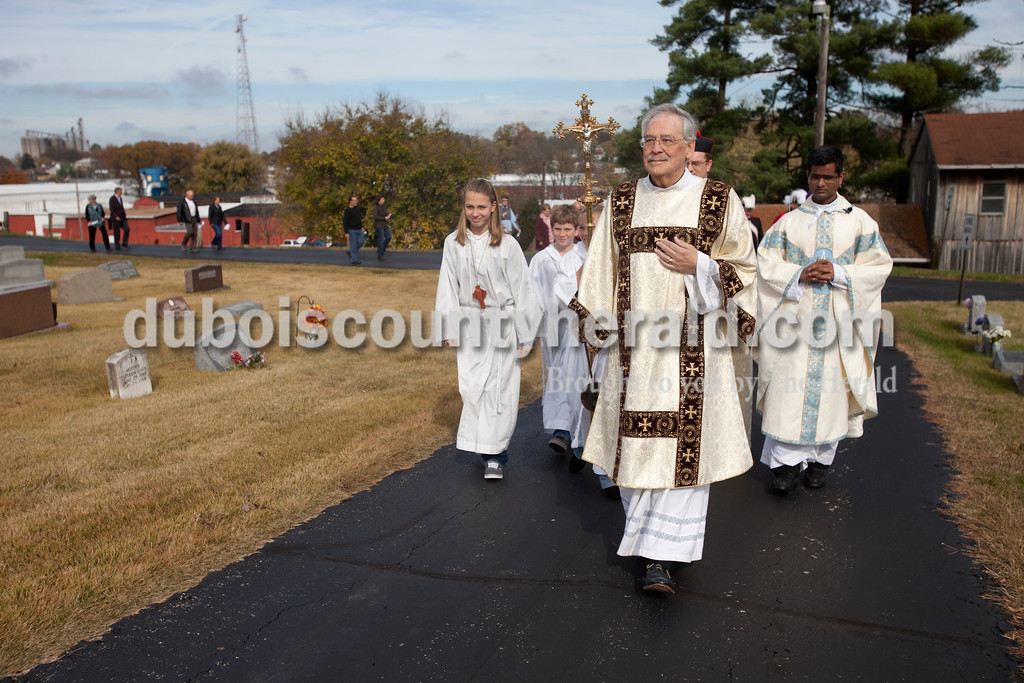 """Erica Lafser/The Herald<br /> Deacon Tom Holsworth of Jasper lead the procession to the """"Monument to the Unborn"""" on Sunday at St. Mary's Church Huntingburg in Huntingburg. This gift of remembrance from the Monsignor Leonard Wernsing Knights of Columbus will be the final monument placed in all Catholic cemeteries throughout Dubois County."""