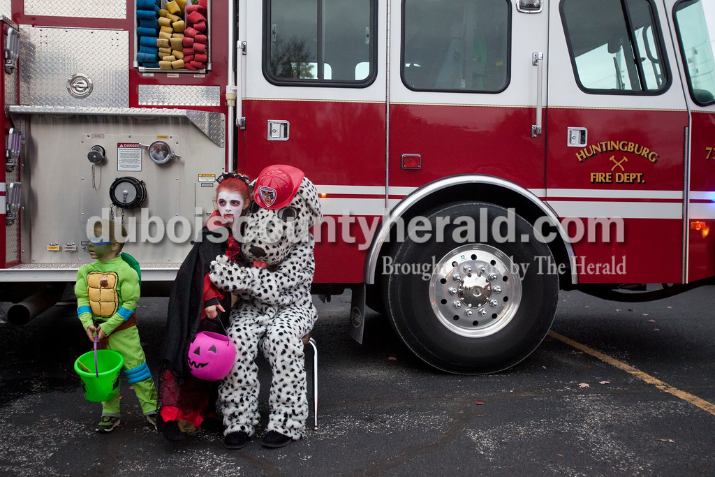 """Erica Lafser/The Herald<br /> Vampire Alexis Rummel of Huntingburg, 8, middle, hugged the Huntingburg departments firehouse dog, Buckets, as her Ninja Turtle brother, Blake, 3, stood near for a photo during the """"Trick-or-Treating at the Fire Station"""" event on Saturday at the Huntingburg City Hall parking lot in Huntingburg. The party geared for 12 year olds and younger let kids look inside fire trucks and police cars."""