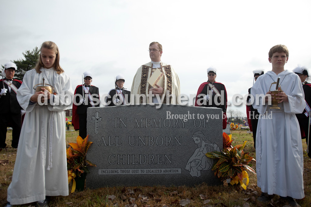 """Erica Lafser/The Herald<br /> Father Ryan Hilderbrand waited for the procession to end before the dedication of the  """"Monument to the Unborn"""" on Sunday at St. Mary's Church Huntingburg in Huntingburg. This gift of remembrance from the Monsignor Leonard Wernsing Knights of Columbus will be the final monument placed in all Catholic cemeteries throughout Dubois County."""