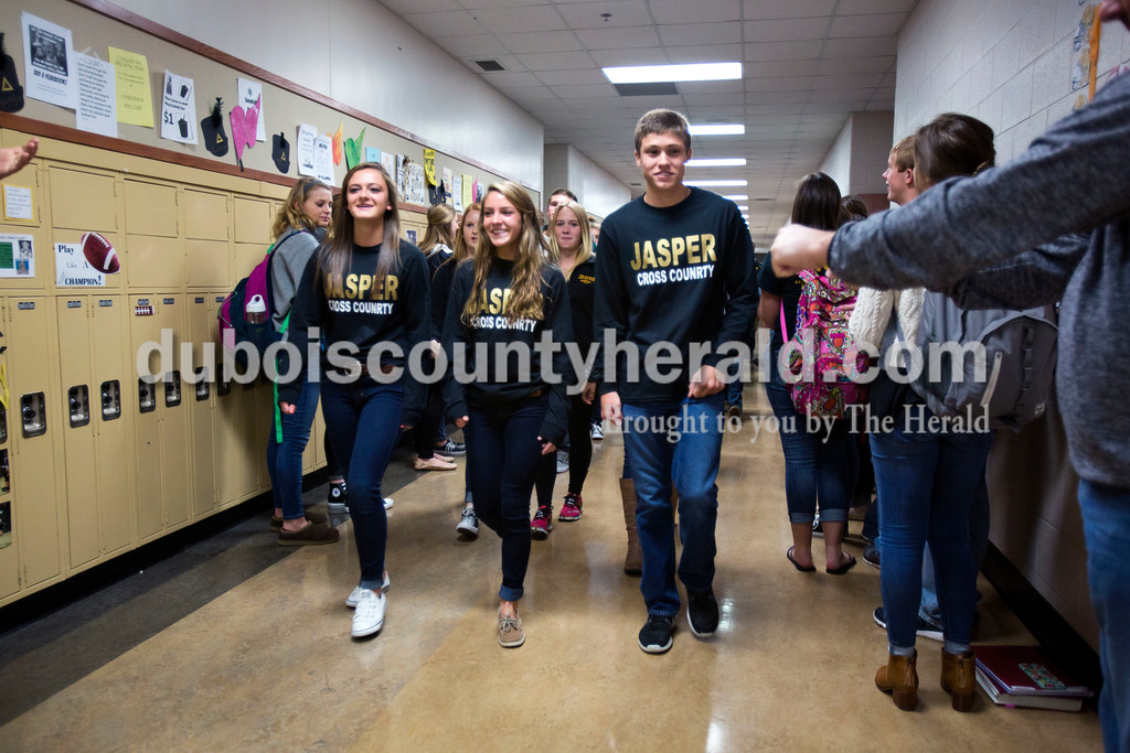 Jasper cross country runners, Tara Cassidy, left, Hannah Welsh and Cale Kilian walked through the halls of Jasper High School on Friday as a send off before their trip up to the state finals race. The cheerleaders and band led them through the halls, as students lined up and cheered them on. The state finals took place on Saturday at Terre Haute's LaVern Gibson Championship Cross Country Course. <br /> <br /> Alisha Jucevic/The Herald