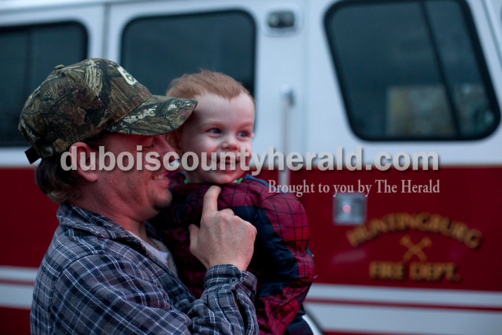 """Erica Lafser/The Herald<br /> Nick Macer of Grandview held his son Austin, 2, during the """"Trick-or-Treating at the Fire Station"""" event on Saturday at the Huntingburg City Hall parking lot in Huntingburg. The party geared for 12 year olds and younger let kids look inside fire trucks and police cars."""