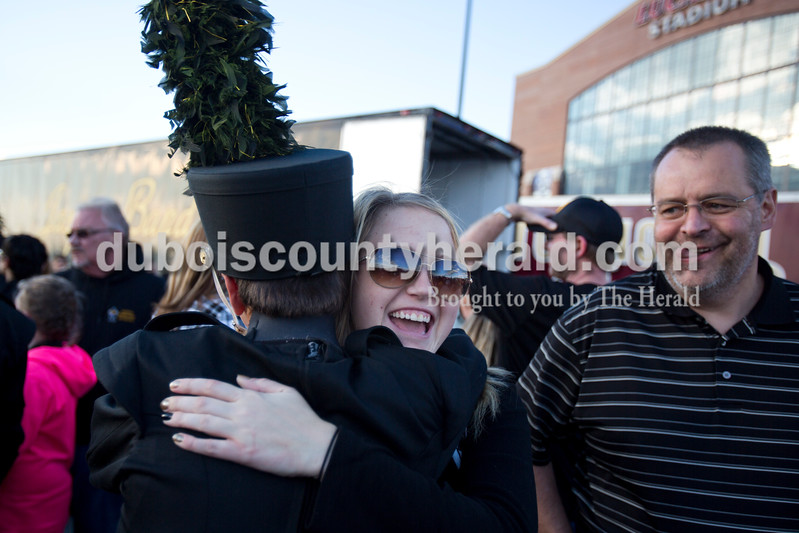 Alisha Jucevic/The Herald <br /> Jasper freshman Ben Stenftenagel embraced his cousin Emma Wininger of Jasper after Jasper's ISSMA State Marching Band competition performance on Saturday at Lucas Oil Stadium in Indianapolis. Ben's father, Bob, stood to their right. The Marching Wildcats placed fourth in ISSMA Open Class B.