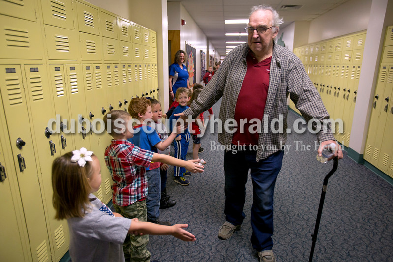 Alisha Jucevic/The Herald <br /> Local veteran Earl Guimond of Kyana high-fived students as the procession of veterans walked through the halls of Pine Ridge Elementary School after a Veterans Day program at the school on Friday morning in Birdseye. The event is held every year to honor the veterans and allow the students to learn more about the veteran's who live in their community.