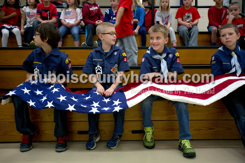 Alisha Jucevic/The Herald <br /> Pine Ridge Elementary school fourth-graders Tyler Oser, Austin DeSchamp, Cody Brames and Seth Striegel sat with the flag before the Veterans Day program began at Pine Ridge Elementary School on Friday morning in Birdseye. The event is held every year to honor the veterans and allow the students to learn more about the veteran's who live in their community.