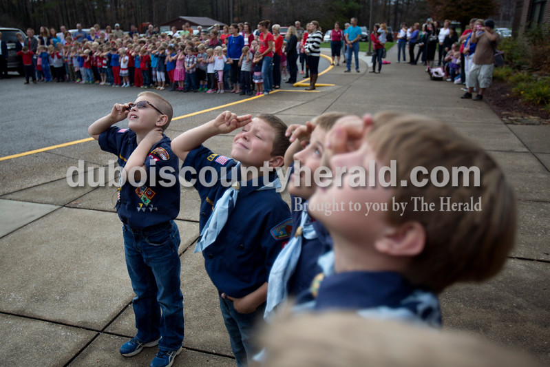 Alisha Jucevic/The Herald <br /> Members of Boy Scout Pack 189 of St. Anthony, and Pine Ridge Elementary School fourth-graders Austin DeSchamp, left, Seth Striegel, Cody Brames and Sam Kluesner saluted the flag during the playing of taps at the Veterans Day program at Pine Ridge Elementary School on Friday morning in Birdseye. To honor the veterans, the students read poems, sang and recited the Pledge of Allegiance during the event.
