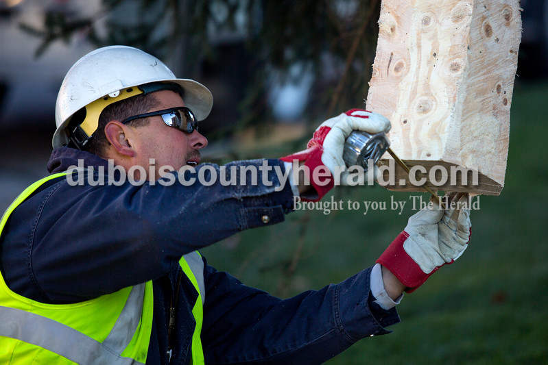 Alisha Jucevic/The Herald <br /> Jasper Municipal Electric Utility worker Casey Hall of Haysville measured the end of the tree trunk to see if it would fit in the hole used to secure it in place on Monday morning on the Square in Jasper.