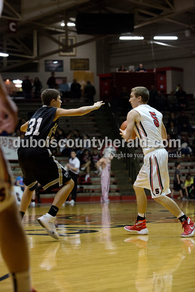 Erica Lafser/The Herald<br /> Southridge's Gaage Fetter looked to pass the ball while Corydon Central's Braydon Beauchamp guarded him during Saturday night's game against Corydon Central at Memorial Gym in Huntingburg. The Raiders won 54-39.