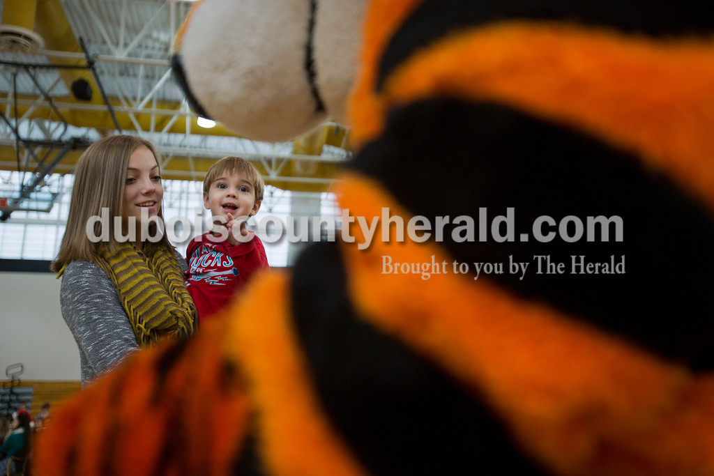Alisha Jucevic/The Herald<br /> Jordan Mehringer of Jasper, 17, held her cousin Gavin Hall, 2, of Hillham, as he was greeted by a Tigger character during the 78th American Legion Post 147's annual community Christmas party at Jasper Middle School on Saturday afternoon. Throughout the weekend Post 147 also brought Santa Claus to visit five different nursing homes around the community.