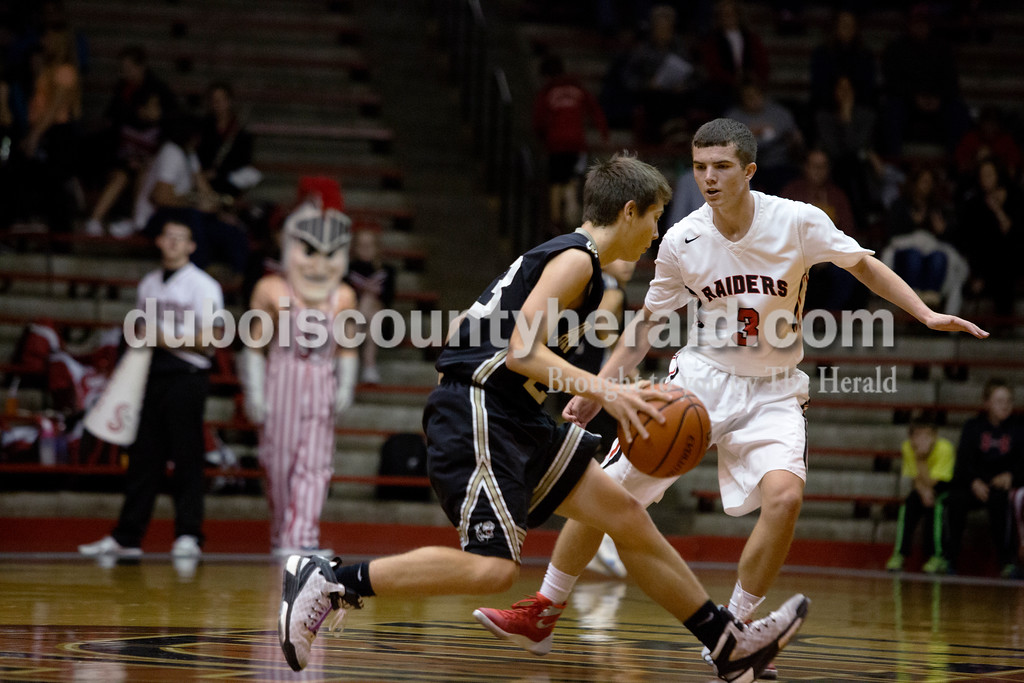 Erica Lafser/The Herald<br /> Southridge's Chase Bland guarded Corydon Central's Clayton Schreck during Saturday night's game at Memorial Gym in Huntingburg. The Raiders won 54-39.