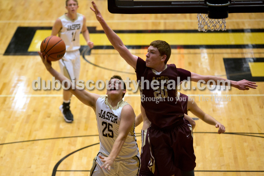 Mount Carmel's Justin Carpenter tried to block a layup from Jasper's Justin Goebel during Saturday night's game against Mount Carmel in Jasper. The Wildcats won 62-37. <br /> Alisha Jucevic/The Herald