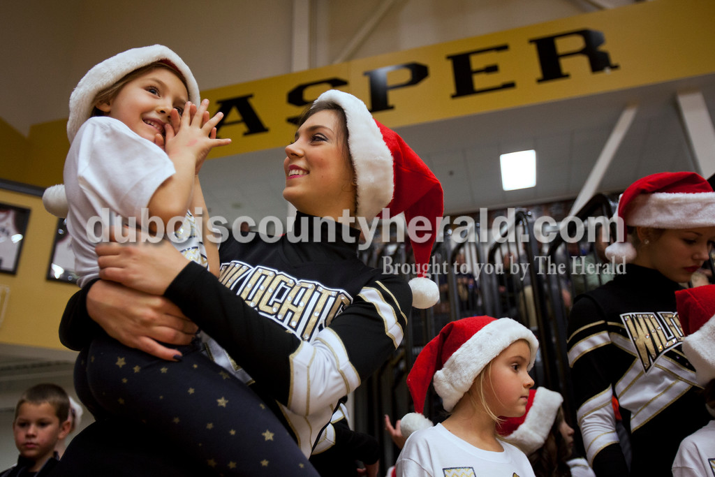 Jasper High School senior Camille Ruff held Marley Hostetter, 5, of Jasper, during Saturday night's basketball game against Mount Carmel in Jasper. The Jasper High School dance team had their Christmas dance clinic earlier in the day and the participants performed with the dance team during halftime of Saturday nights game.<br /> Alisha Jucevic/The Herald