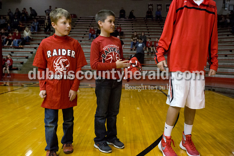 Erica Lafser/The Herald<br /> Lane Kratzer of Huntingburg, 8, left, and Heith Steckler of St. Henry, 7, waited for the Southridge players to run by for the starting lineup before Saturday night's game against Corydon Central at Memorial Gym in Huntingburg. The Raiders won 54-39.