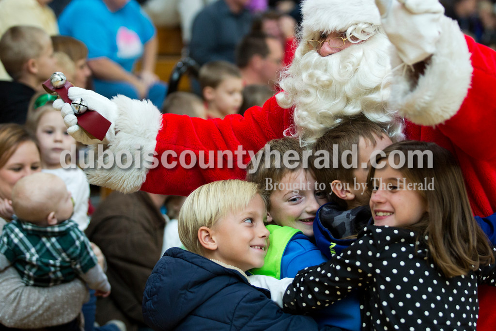 Alisha Jucevic/The Herald<br /> Joel Levy, 7, Ethan Bauer, 7, Carson Bauer, 9, and Mickinzie Marks, 8, all of Jasper embraced Santa during the 78th American Legion Post 147's annual community Christmas party at Jasper Middle School on Saturday afternoon. Throughout the weekend Post 147 also brought Santa Claus to visit five different nursing homes around the community.