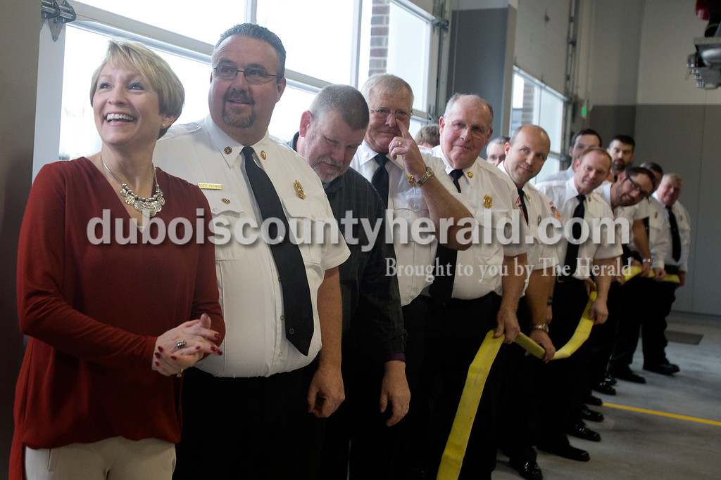 Erica Lafser/The Herald<br /> Lieutenant Governor Sue Ellspermann of Ferdinand, left, celebrated the uncoupling ceremony at the rededication of Fire Station 2 in Huntingburg on Sunday. The line of Huntingburg firefighters held the hose that her and Huntingburg Mayor Denny Spinner uncoupled. This is the firefighter's version of a ribbon cutting.