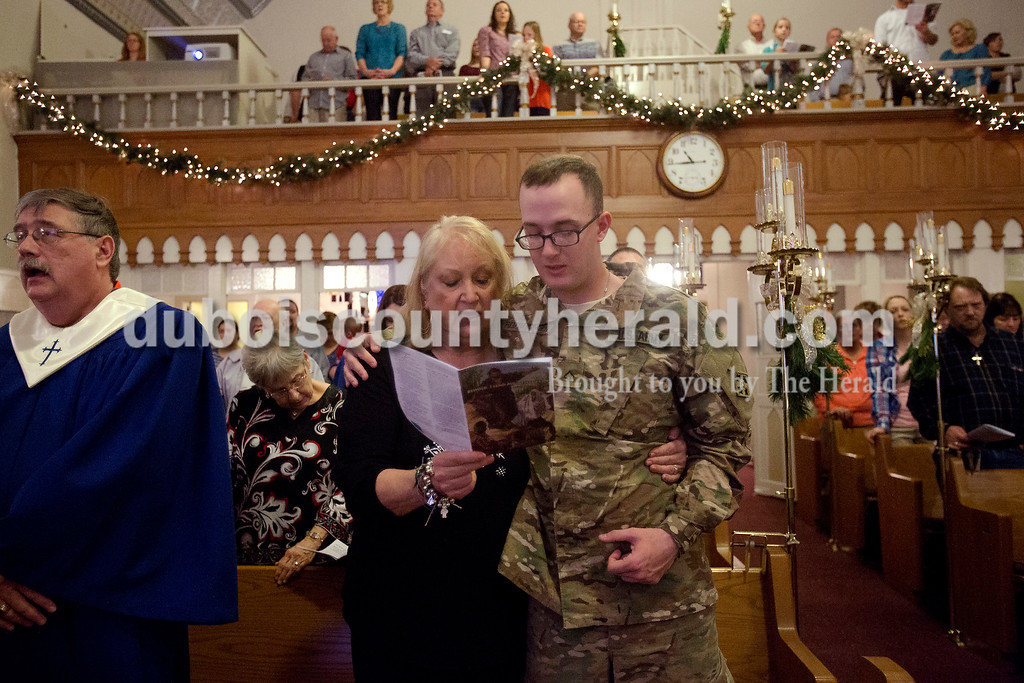 Erica Lafser/The Herald<br /> Melanie Ferber of Holland, left, wrapped her grandson, Huntingburg native Austin Reutepohler, right, in her arms while they sang at St. James Lutheran Church in Holland on Sunday. Reutepohler surprised Ferber and her husband, Walt, with his presence during the service. After being gone for a year to an eight month deployment in Kuwait and being stationed in Fort Carson, Colorado, this was his first time seeing them face to face.