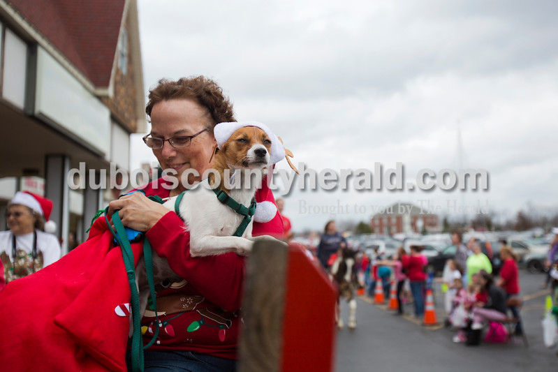 Diane Deom of Lamar rode on the Hay Rides of Santa Claus float with her dog, Bella, during Santa Claus' annual Christmas parade on Saturday afternoon. The town continued their festive celebrations over the weekend with chestnut roasting, the Santa Claus Land of Lights, the Das Nikolaus Fest, visiting with an Elf on the North Pole Network and much more. <br /> Alisha Jucevic/The Herald