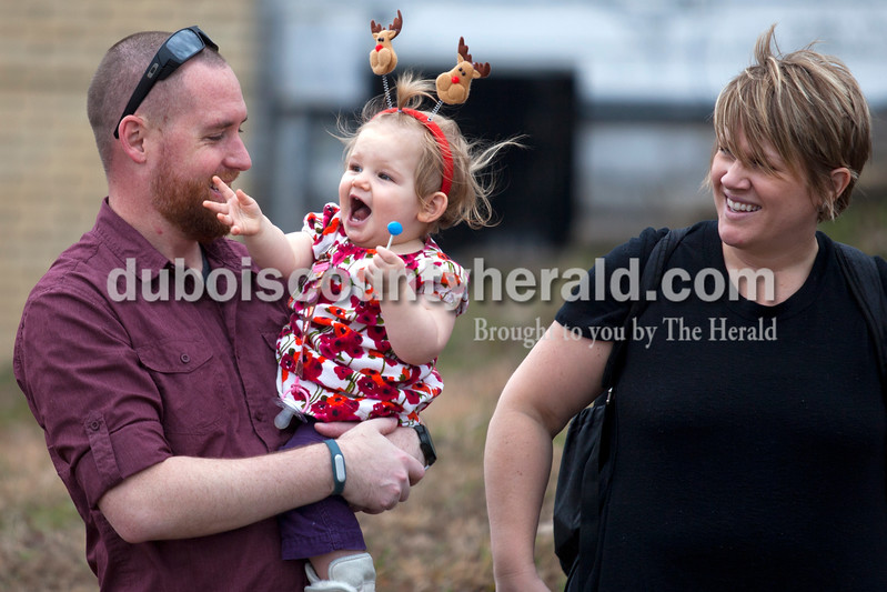 Lyla Steier, 1, reacted as watched the beginning of the parade with her parents Brian and Audrey Steier, all of New Albany, during Santa Claus' annual Christmas parade in downtown Santa Claus on Saturday afternoon. The town continued their festive celebrations over the weekend with chestnut roasting, the Santa Claus Land of Lights, the Das Nikolaus Fest, visiting with an Elf on the North Pole Network and much more. <br /> Alisha Jucevic/The Herald