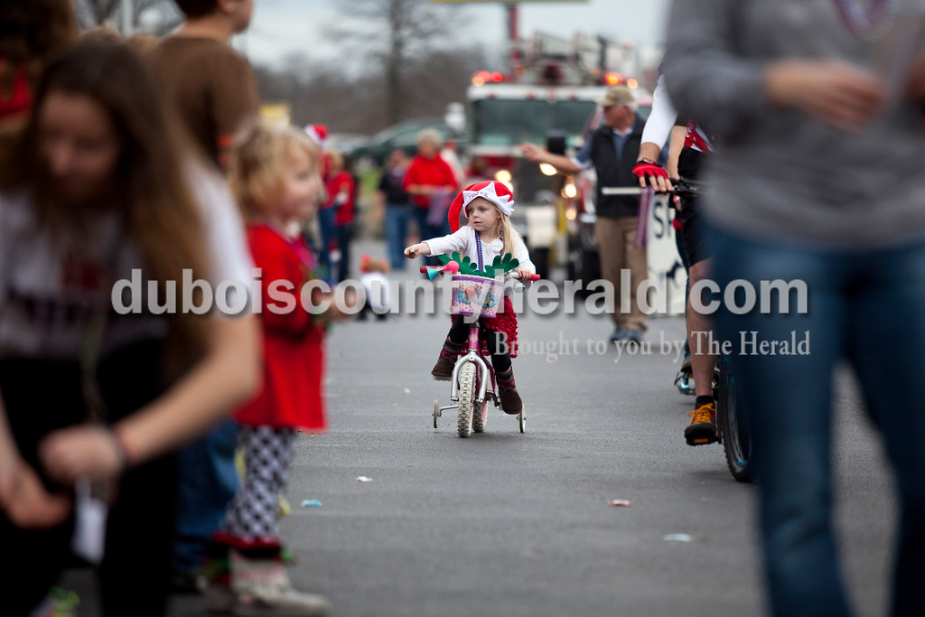 Kendall Flannagan of Santa Claus, 5, handed out candy with the Trails of Santa Claus float during Santa Claus' annual Christmas parade on Saturday afternoon. The town continued their festive celebrations over the weekend with chestnut roasting, the Santa Claus Land of Lights, the Das Nikolaus Fest, visiting with an Elf on the North Pole Network and much more. <br /> Alisha Jucevic/The Herald