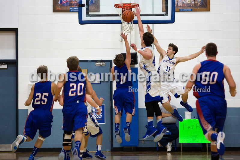 Alisha Jucevic/The Herald<br /> Northeast Dubois' Keigan Meyer and Sidney Schott jumped to block a sot by Tecumseh's Carson White during Saturday night's game in Dubois. The Jeeps won 53-46.