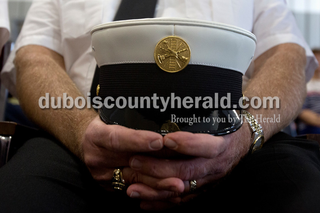 Erica Lafser/The Herald<br /> Huntingburg 1st Assistant Chief Glen Kissling held his hat while he sat through the speakers during the uncoupling ceremony at the rededication of Fire Station 2 in Huntingburg on Sunday.