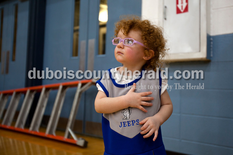 Alisha Jucevic/The Herald<br /> Haley Bayer, 2, of Jasper looked up at the American flag during the national anthem during Saturday night's game against Tecumseh in Dubois. The Jeeps won 53-46.